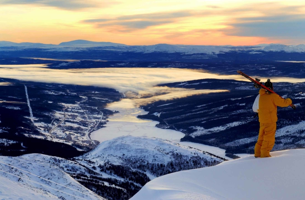 A man with skies is looking over the Åre Valley